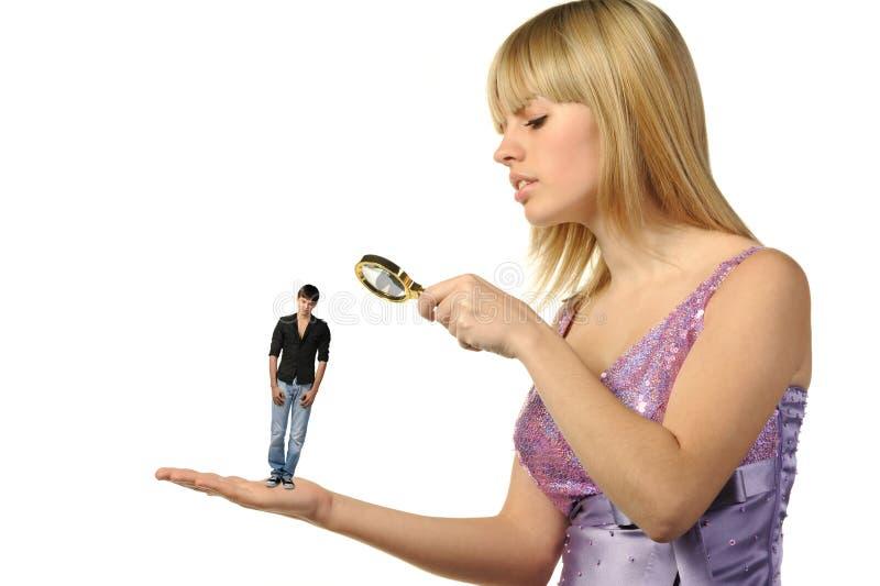 A menina que considera o indivíduo através de um magnifier fotos de stock