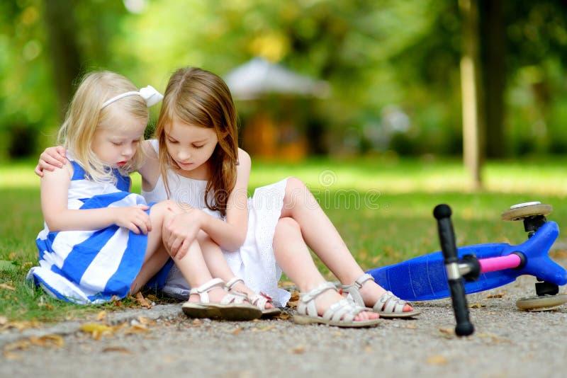 Menina que consola sua irmã depois que caiu ao montar seu 'trotinette' imagens de stock royalty free