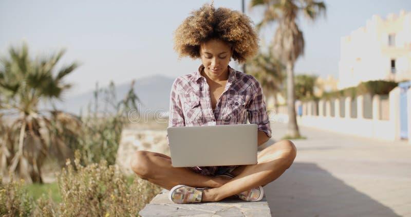 Menina que consulta um portátil em um banco fotografia de stock royalty free