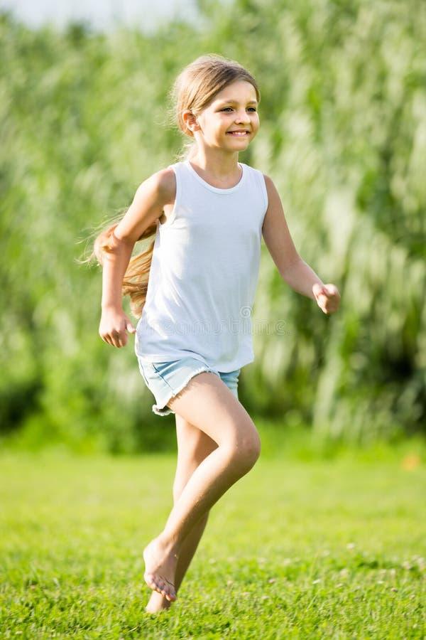 Menina que corre e que salta na grama fotos de stock royalty free