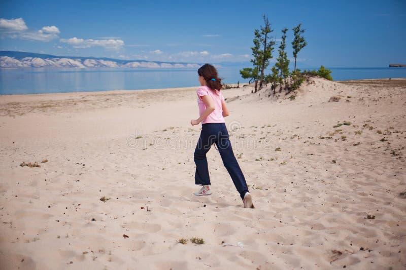 Menina que corre na areia da ilha de Olkhon imagem de stock