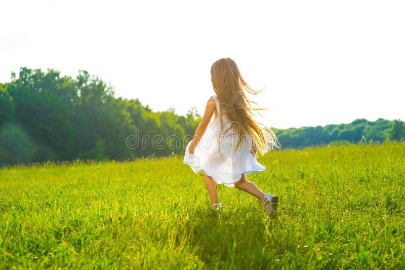 Menina que corre na grama verde imagem de stock royalty free