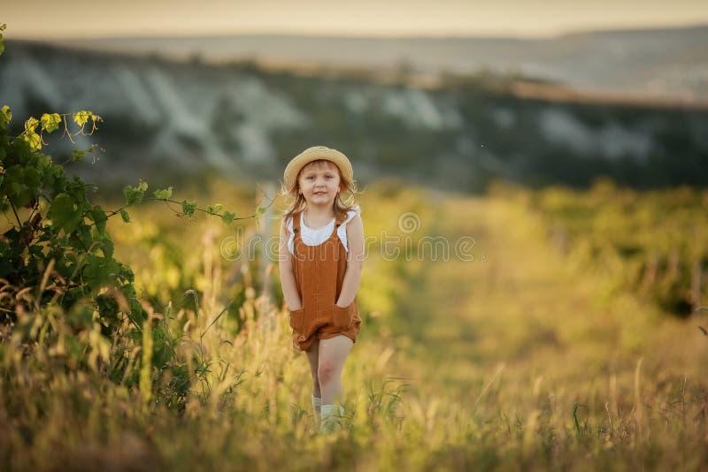 Menina que corre na grama verde Noite morna bonita do ver?o imagens de stock