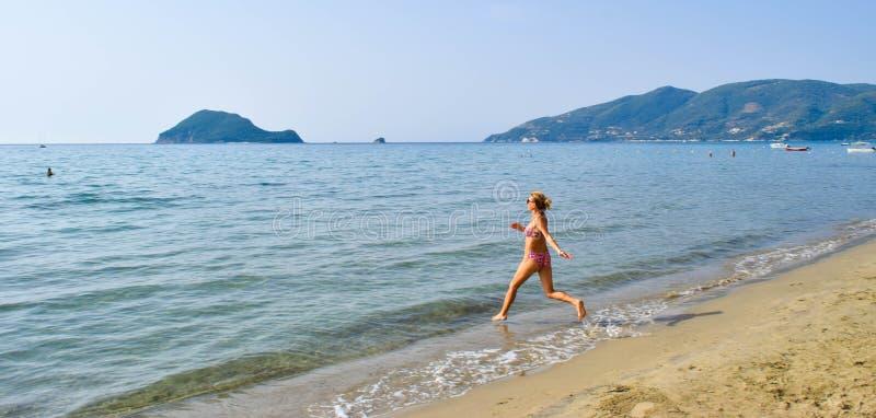 Menina que corre no mar foto de stock royalty free
