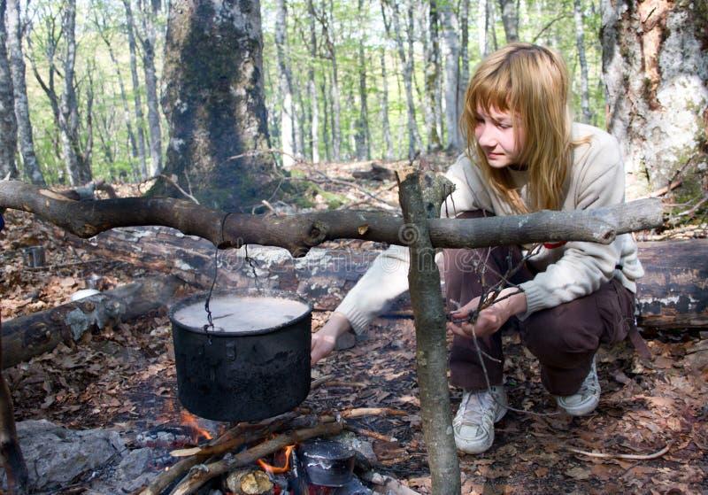 Menina que cozinha o alimento no incêndio no acampamento fotos de stock