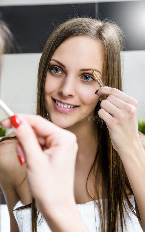 Menina que dá forma às sobrancelhas com tweezer imagens de stock royalty free