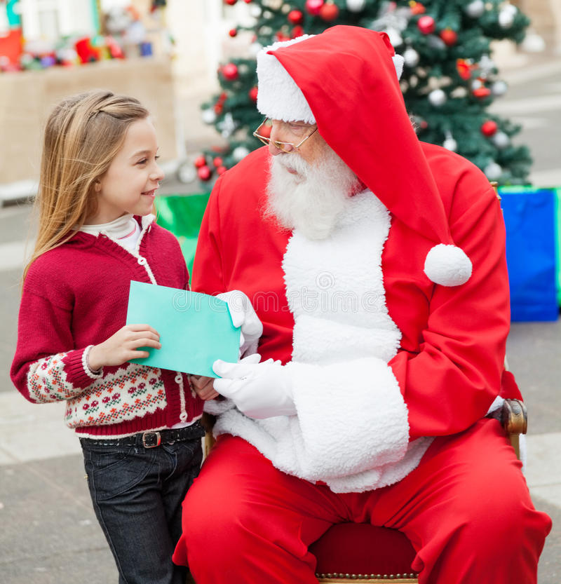 Menina que dá a lista de objetivos pretendidos a Santa Claus fotografia de stock royalty free
