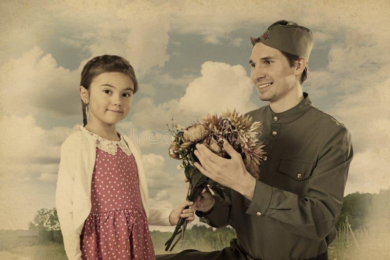 Menina que dá o grupo de flores ao soldado soviético imagens de stock