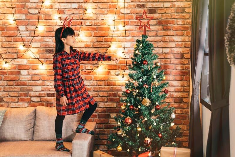 Menina que decora a árvore de Natal em casa imagens de stock