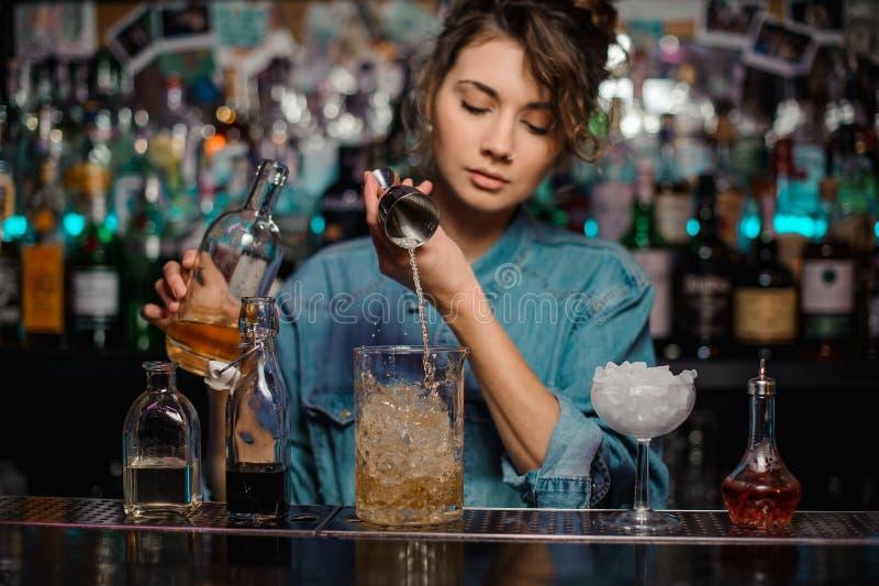 A menina que derrama ao copo de vidro da medição com gelo cuba uma bebida alcoólica do jigger imagens de stock