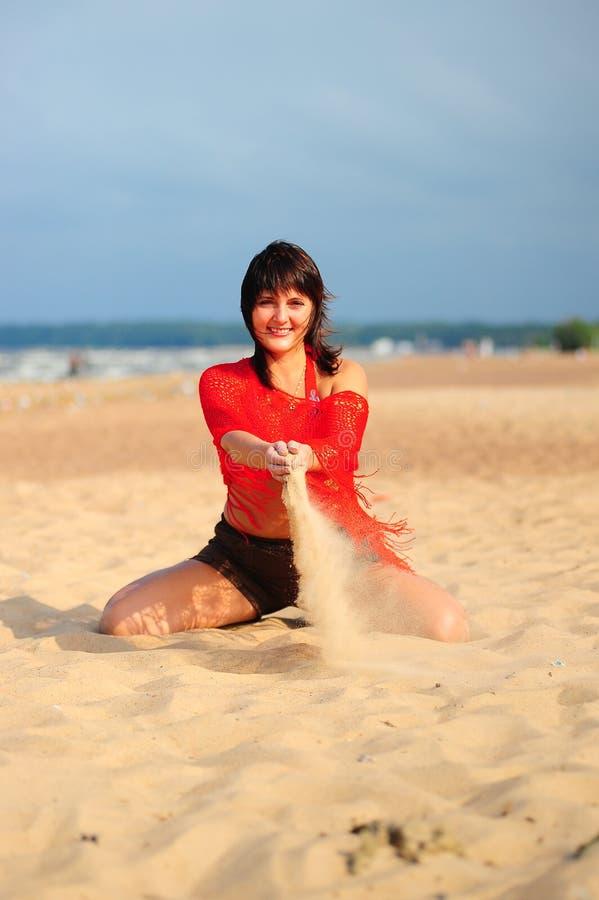 A menina que derrama para fora a areia imagem de stock