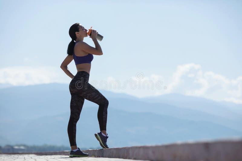 Menina que descansa após o exercício, água da bebida das garrafas imagem de stock