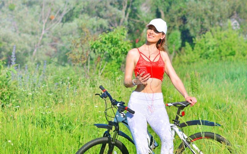 Menina que descansa em uma bicicleta após biking fora e apreciar a escuta a música de um smartphone foto de stock royalty free