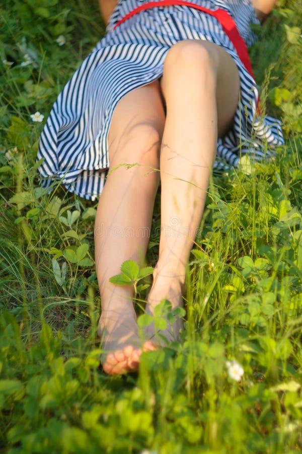 Menina que descansa na grama no parque em um dia ensolarado do verão Pés desencapados e vestido imagens de stock royalty free