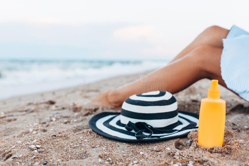 Menina que descansa na praia, pés bronzeados bonitos contra o mar azul, frasco do creme fotografia de stock