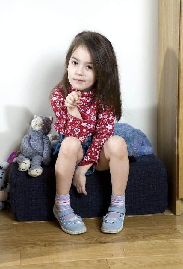 menina que desgasta a camisa vermelha que senta-se no hassock imagens de stock
