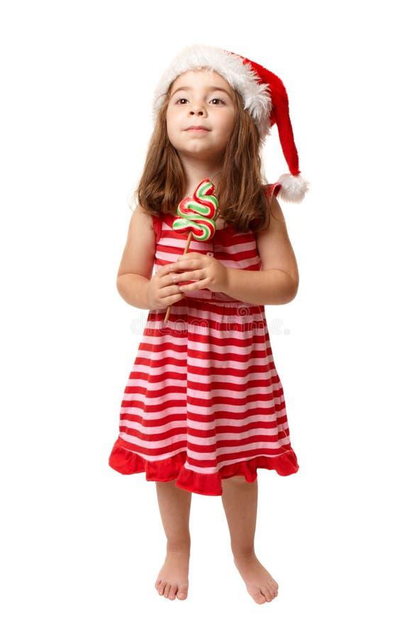 Menina que desgasta doces da terra arrendada do chapéu de Santa imagem de stock
