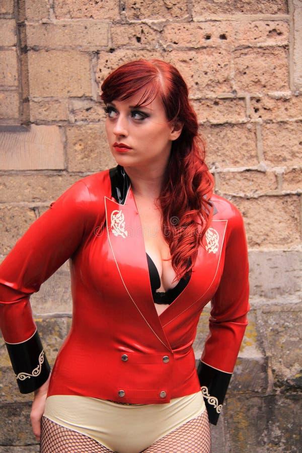 Menina que desgasta o vestido vermelho do látex fotografia de stock royalty free