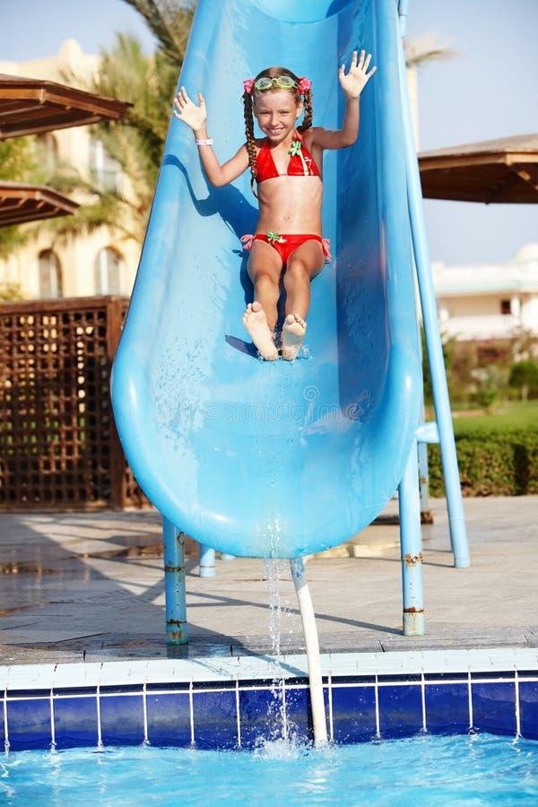 Menina que desliza para baixo a corrediça de água. imagens de stock royalty free