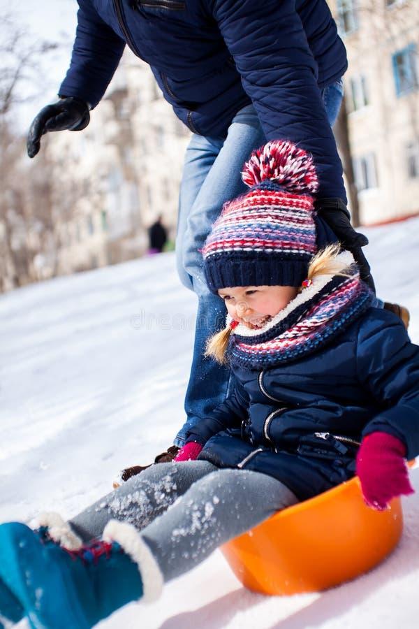 Menina que desliza para baixo do monte da neve com seu pai fotografia de stock