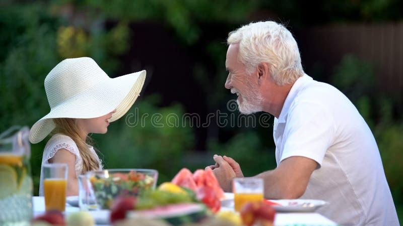 Menina que diz a história de excitação ao avô, tempo da despesa junto, relacionamento fotografia de stock