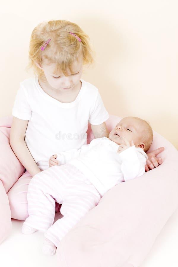 Menina que embala a uma irmã idosa do bebê do mês fotos de stock royalty free