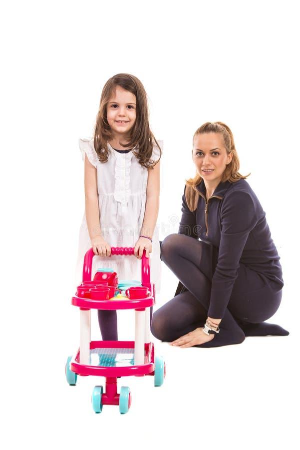 Menina que empurra o brinquedo do pram imagem de stock
