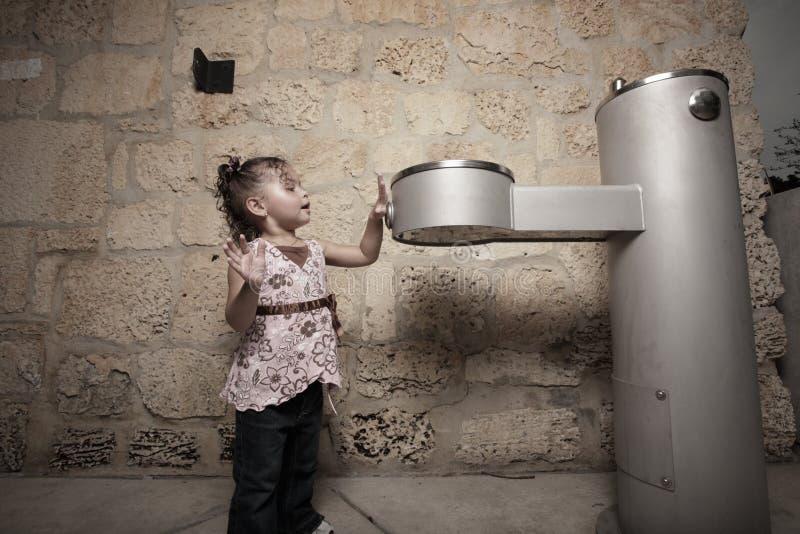 Menina que empurra a tecla da fonte de água fotos de stock royalty free