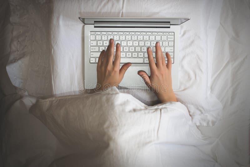 Menina que encontra-se com um portátil na cama coberta pela cobertura A mulher não pode dormir e não tem que trabalhar tarde na n foto de stock