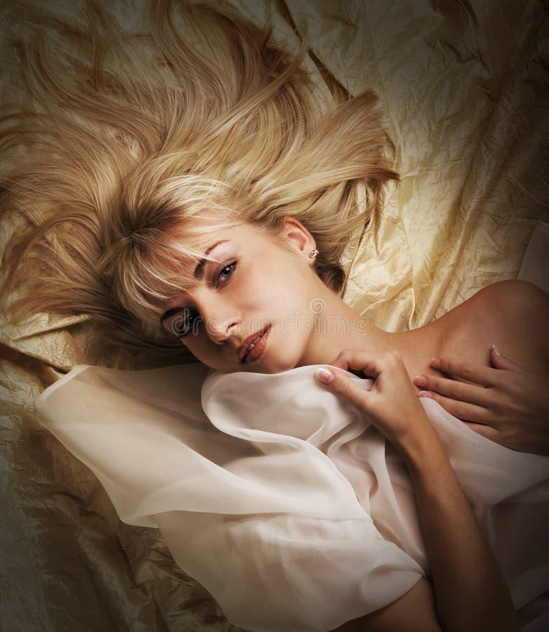 Menina que encontra-se em uma cama foto de stock