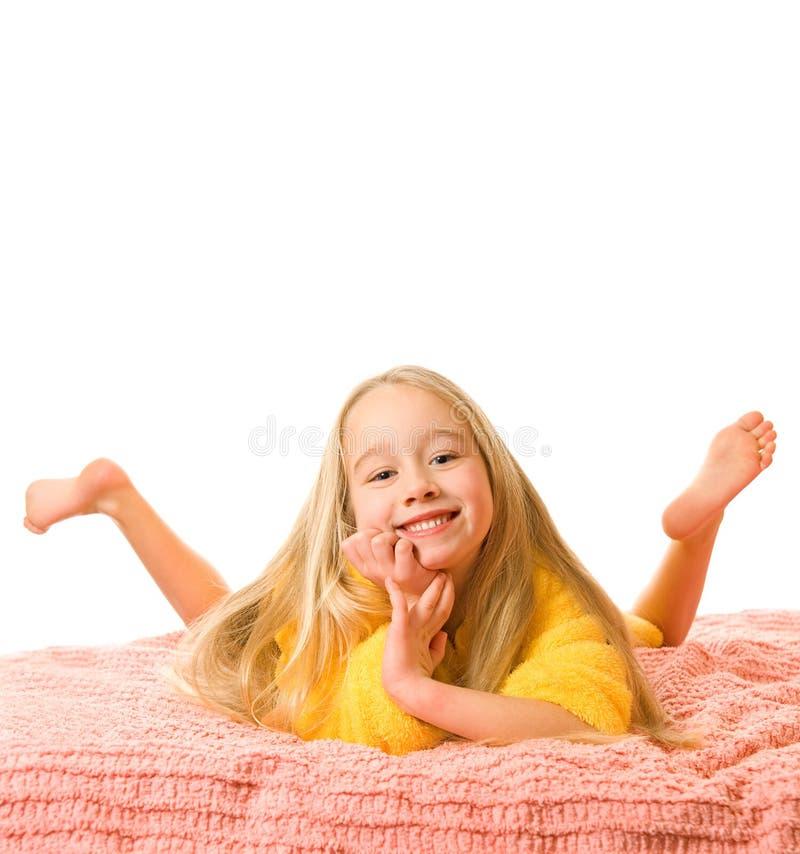 Menina que encontra-se em uma cama imagens de stock