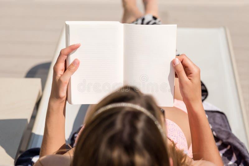 Menina que encontra-se lendo um livro foto de stock