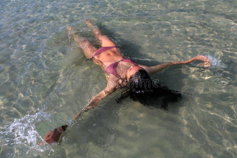 Menina que encontra-se na água fotos de stock