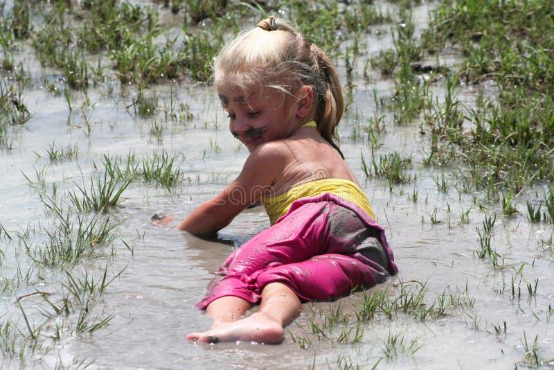 Menina que encontra-se na água enlameada foto de stock royalty free