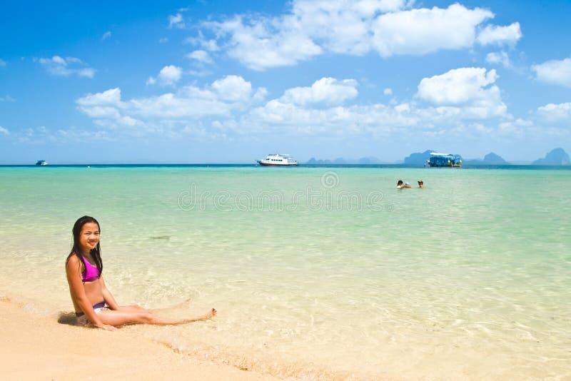 Menina que encontra-se na água na praia fotos de stock