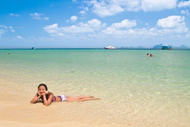 Menina que encontra-se na água na praia fotografia de stock royalty free
