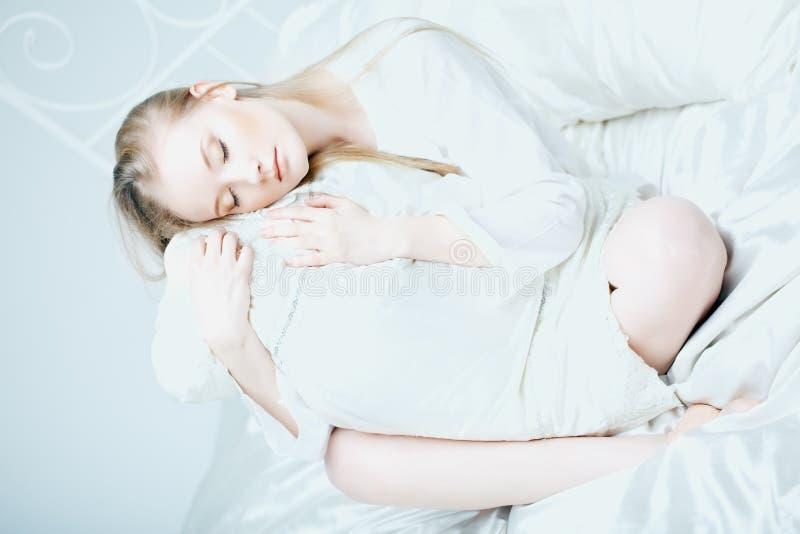 Menina que encontra-se na cama foto de stock royalty free