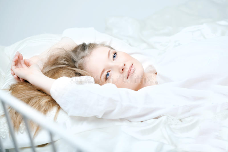 Menina que encontra-se na cama fotos de stock royalty free