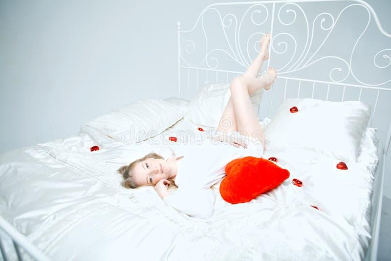 Menina que encontra-se na cama com um coração vermelho imagem de stock royalty free