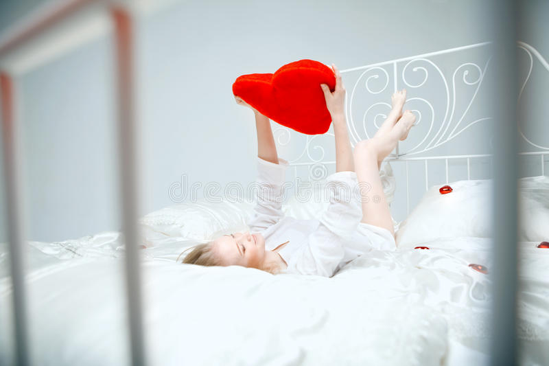 Menina que encontra-se na cama com um coração vermelho fotos de stock royalty free