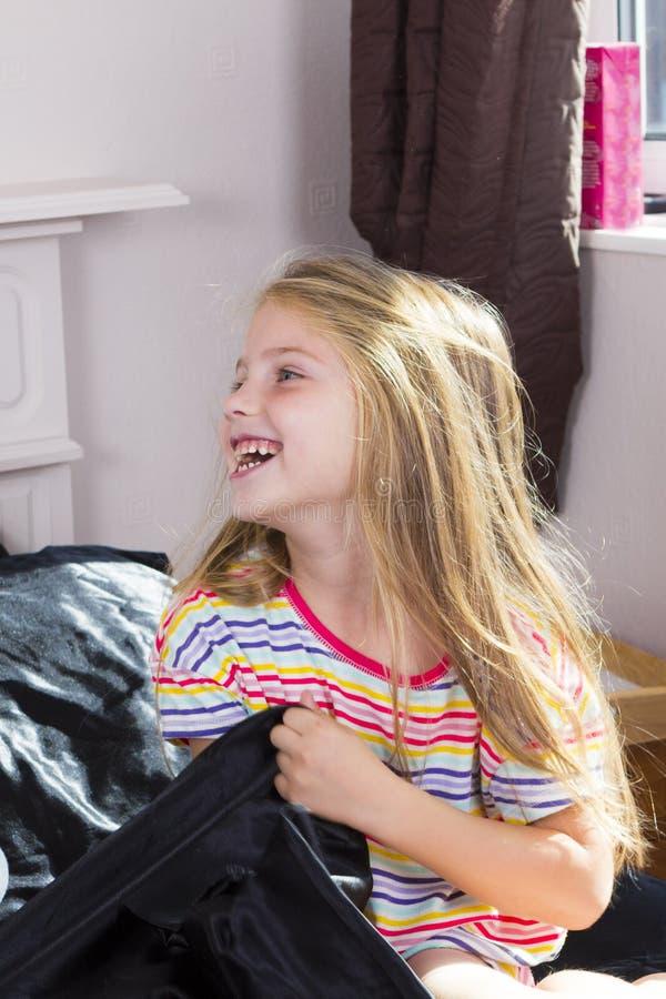 Menina que encontra-se na cama em casa foto de stock royalty free