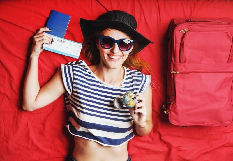 Menina que encontra-se na cama vermelha com bilhete fotografia de stock