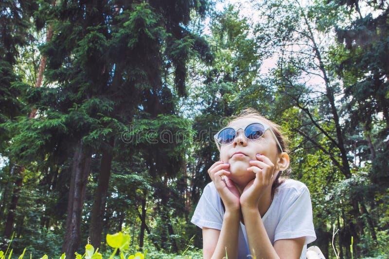 Menina que encontra-se na grama e que olha acima, imagem tonificada imagem de stock royalty free