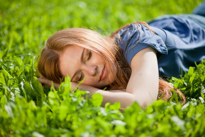 Menina que encontra-se na grama e que dorme pacificamente fotografia de stock royalty free