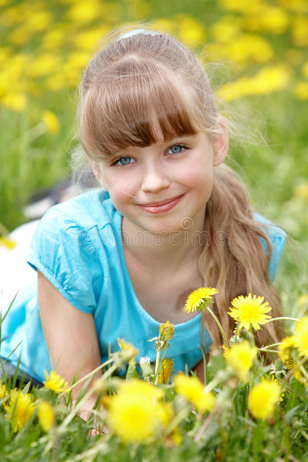 Menina que encontra-se na grama na flor. fotografia de stock