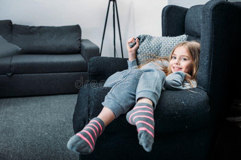 Menina que encontra-se na poltrona com descanso e que olha a câmera fotografia de stock