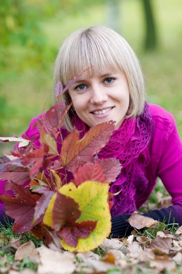 Menina que encontra-se nas folhas da queda foto de stock