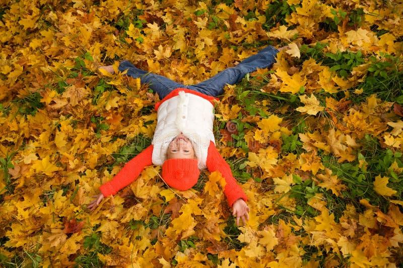 Menina que encontra-se nas folhas de outono imagem de stock royalty free