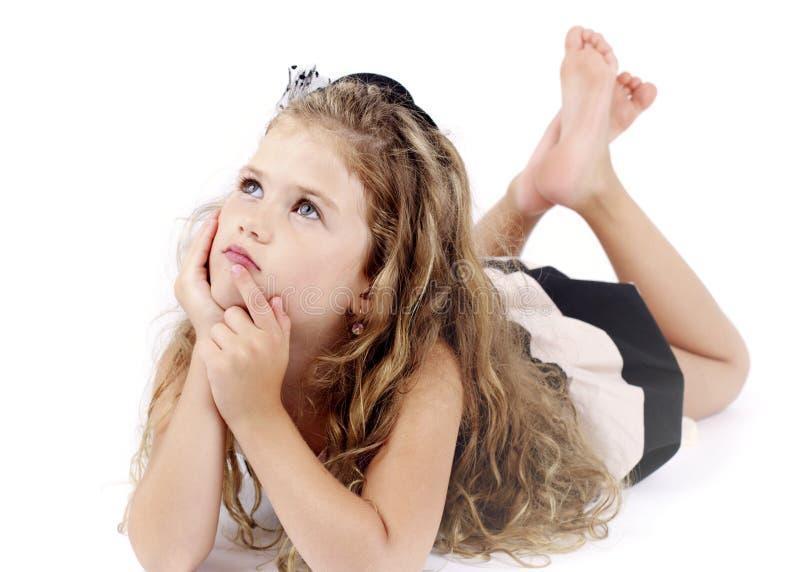 Menina que encontra-se no assoalho e no sonho imagens de stock royalty free
