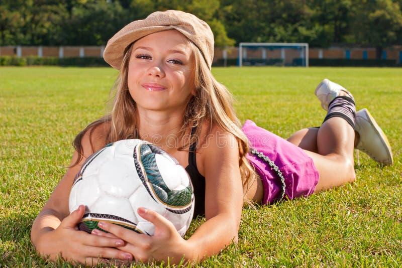 Menina que encontra-se no campo de futebol imagens de stock